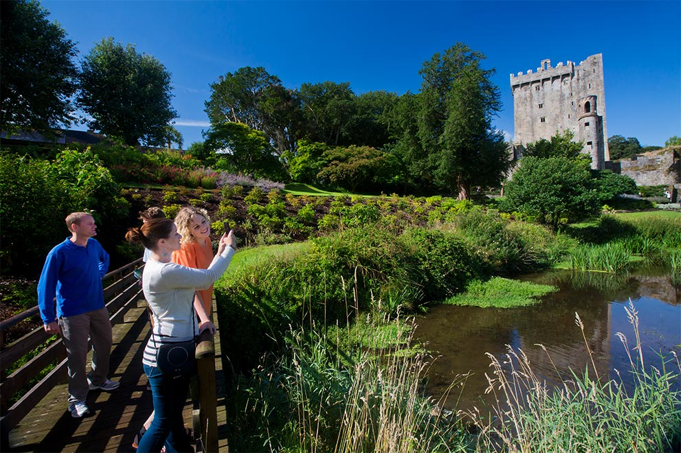 Three tourists photographing Cork's famous Blarney Castle, all the while enjoying a stroll in the gorgeous gardens.
